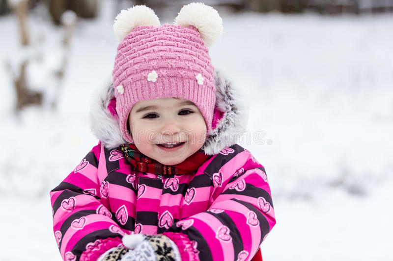 Cute little girl having fun outdoor on nature at winter. Portrait of little girl in pink jacket with red scarf and pink hat in snowy park at winter stock photos