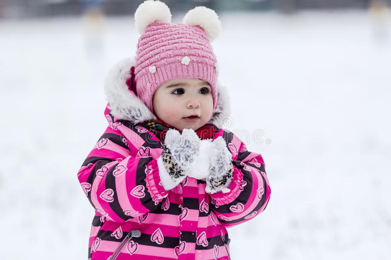 Cute little girl having fun outdoor on nature at winter. Portrait of little girl in pink jacket with red scarf and pink hat in snowy park at winter royalty free stock photo