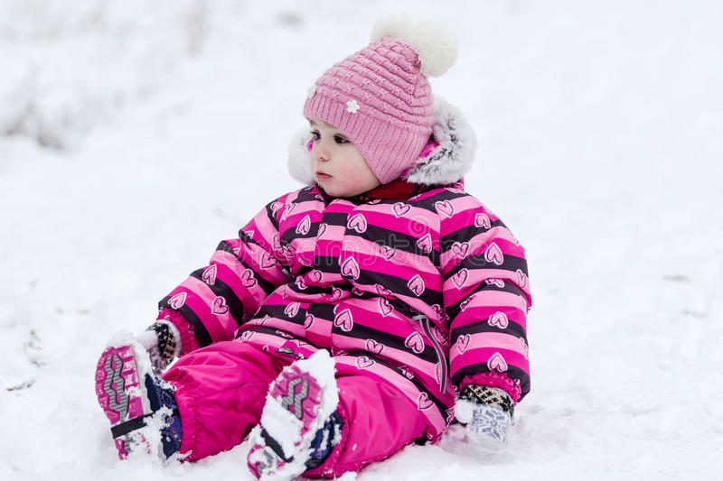 Cute little girl having fun outdoor on nature at winter. Portrait of little girl in pink jacket with red scarf and pink hat in snowy park at winter stock photo