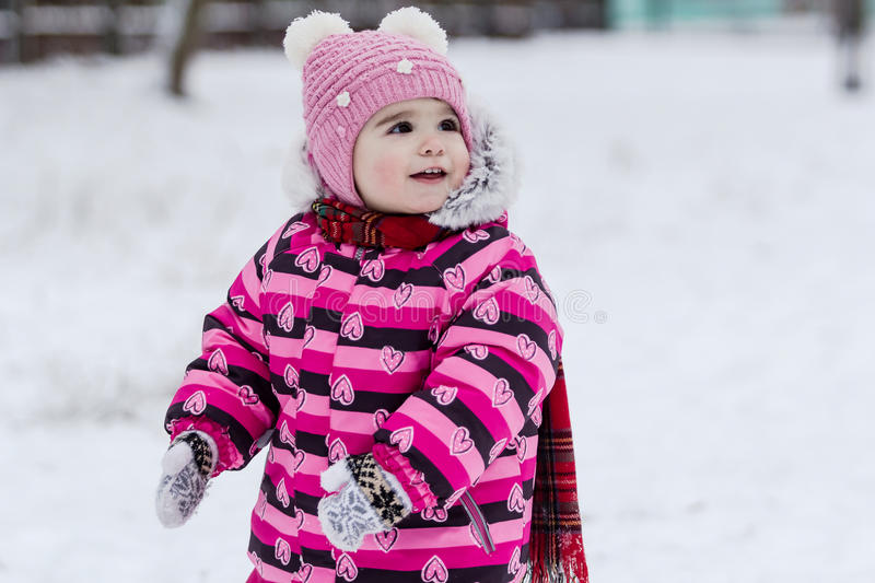 Cute little girl having fun outdoor on nature at winter. Portrait of little girl in pink jacket with red scarf and pink hat in snowy park at winter stock photography