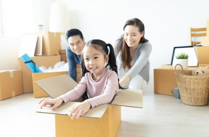 Cute little girl having fun with parents while riding in cardboard box in new house. Moving house day and express delivery royalty free stock image