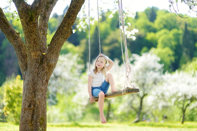 Cute little girl having fun on a swing in blossoming old apple tree garden outdoors on sunny spring day stock image