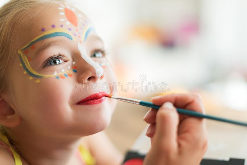 Cute little girl having her face painted for Halloween party. Halloween or carnival family lifestyle background. Face painting. royalty free stock images