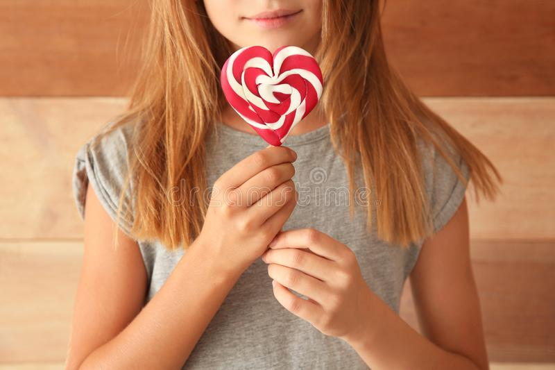 Cute little girl with heart-shaped lollipop on wooden background, closeup royalty free stock photos