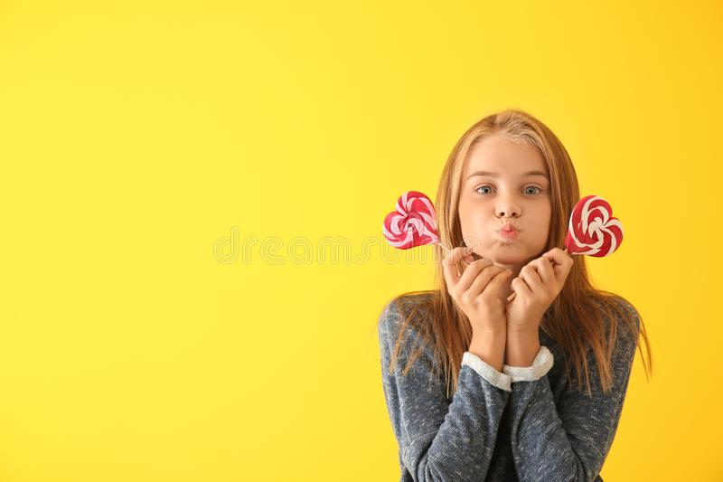 Cute little girl with heart-shaped lollipops on color background stock images