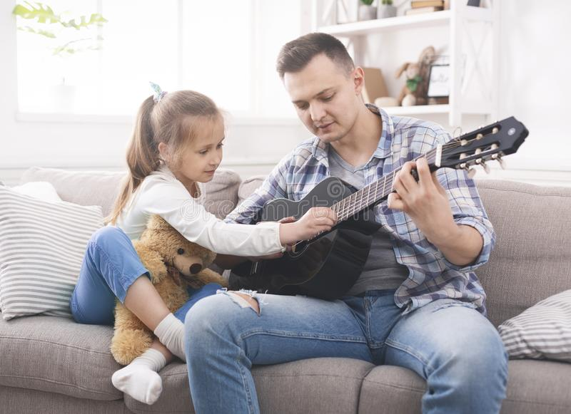 Cute little girl is helping her father to play guitar royalty free stock images