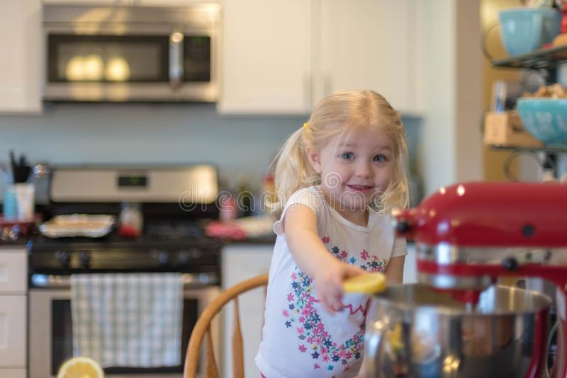 Cute little girl helping in the kitchen stock photos