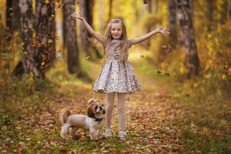 Cute little girl with her dog in autumn park. Lovely child with dog walking in fallen leaves. royalty free stock image