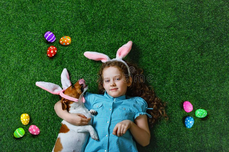 Cute little girl and her dog with rabbit ears lying on green grass royalty free stock images