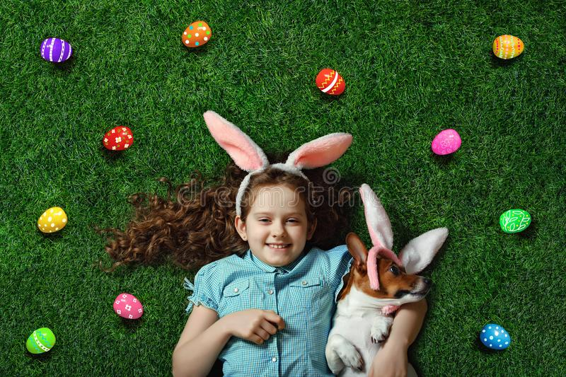 Cute little girl and her dog with rabbit ears lying on green grass. royalty free stock photo