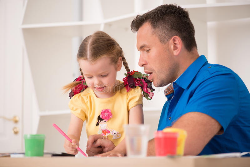 Cute Little Girl And Her Father Painting Together Stock Photo