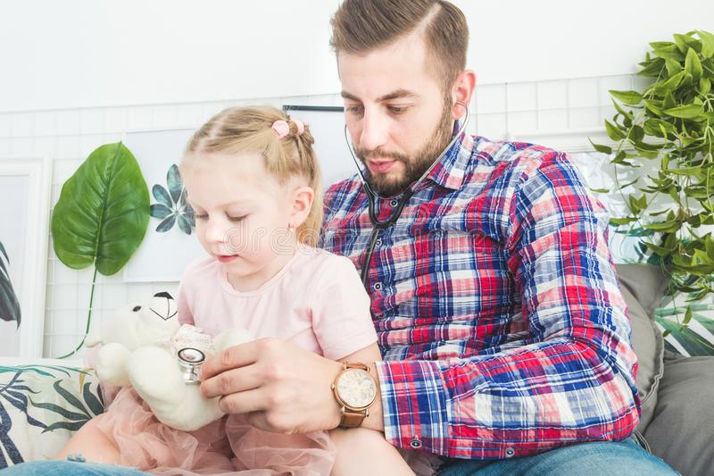 Cute little girl and her father are playing doctor at home. stock images