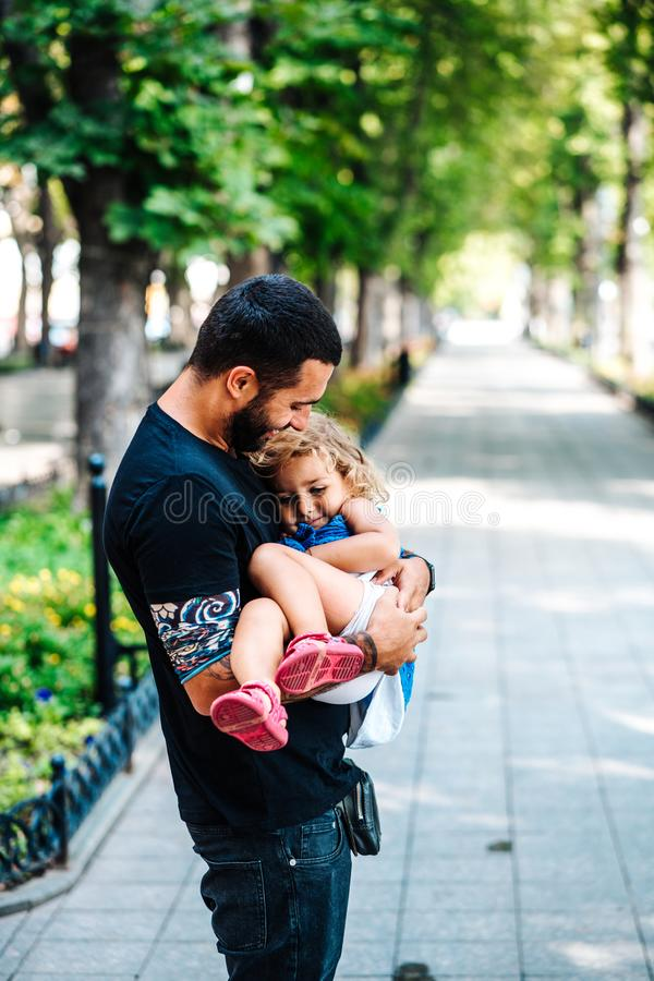 Cute little girl in her father`s arm. In the street stock photos