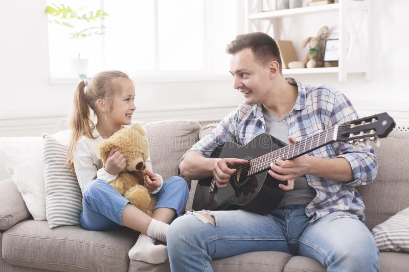 Cute little girl and her handsome father are playing guitar royalty free stock photos