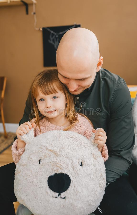 Cute little girl and her handsome young bald dad are holding pillow of teddy bear. Kid looking at camera stock photo