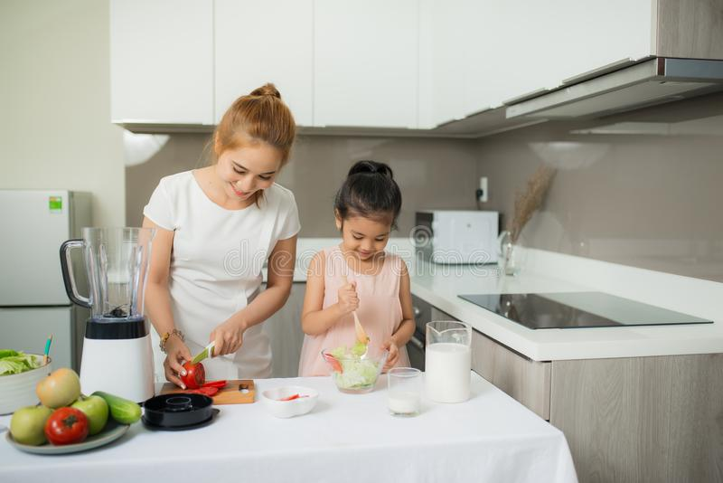 Cute little girl and her mom in chef`s hats are cutting vegetables cooking a salad and smiling royalty free stock photo
