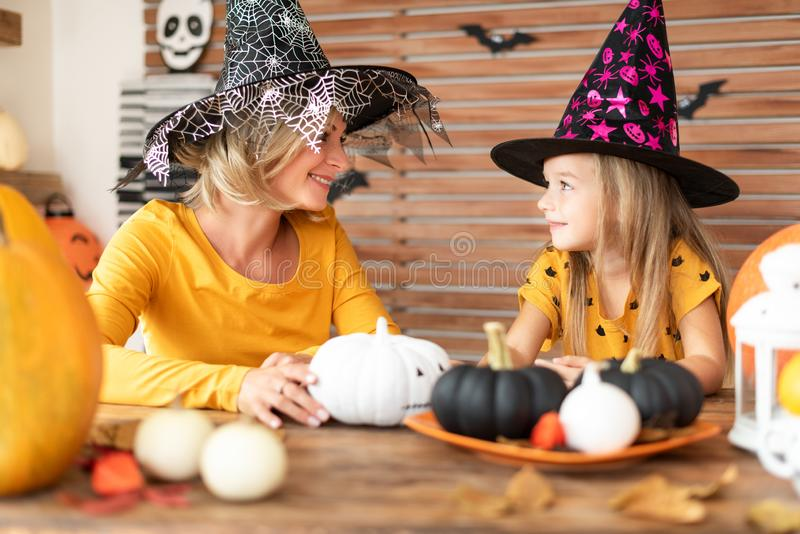 Cute little girl and her mother, both in witch costumes, sitting behind a table in Halloween theme decorated room. royalty free stock image