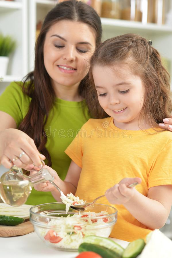 Cute little girl with her mother cooking together royalty free stock image