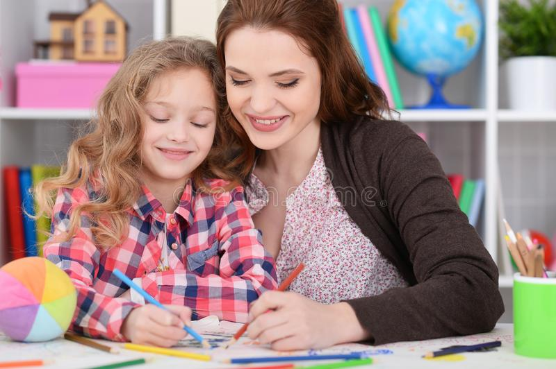 Little girl with her mother drawing royalty free stock image