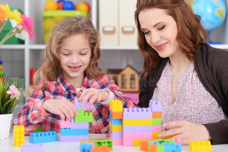 Cute little girl and her mother playing colorful plastic blocks stock images