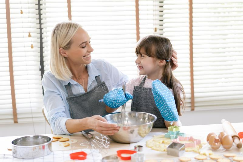 Cute little girl and her mother preparing the dough in the kitchen at home.Happy family and people concept.Mother`s day stock photos