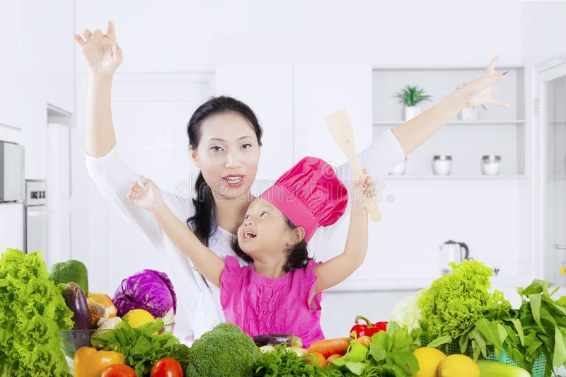 Cute girl and mother with vegetables royalty free stock photography