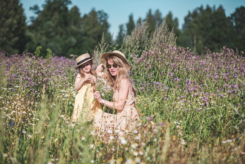 Cute little girl with her mother walking in the flowers field royalty free stock image