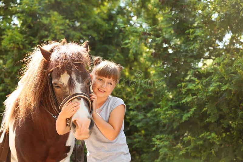 Cute little girl with her pony in park royalty free stock images