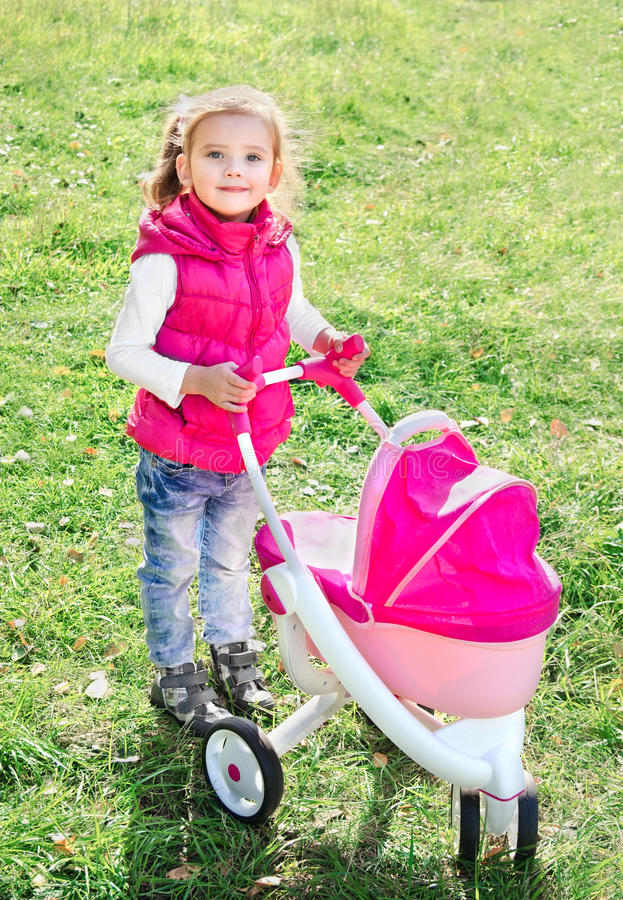 Cute little girl with her toy carriage royalty free stock images