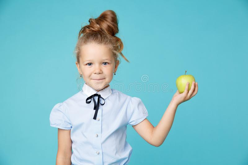 Cute little girl holding apple isolated over the blue background. stock photo