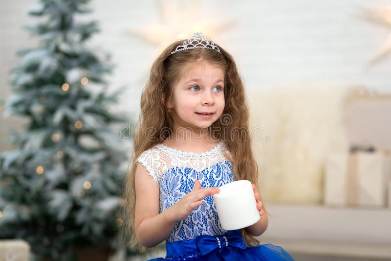 Cute little girl holding an artificial candle in her hands for home decoration for the Christmas holidays. Child-friendly scenery stock image