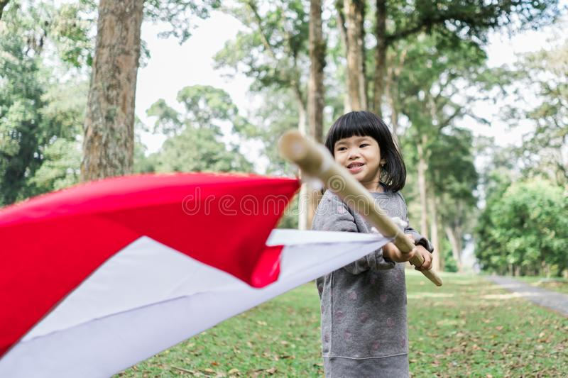 Cute little girl holding big stick of nation flag with smile. In the garden stock photography