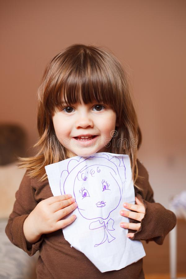 Cute little girl holding a drawing in front of her stock photos