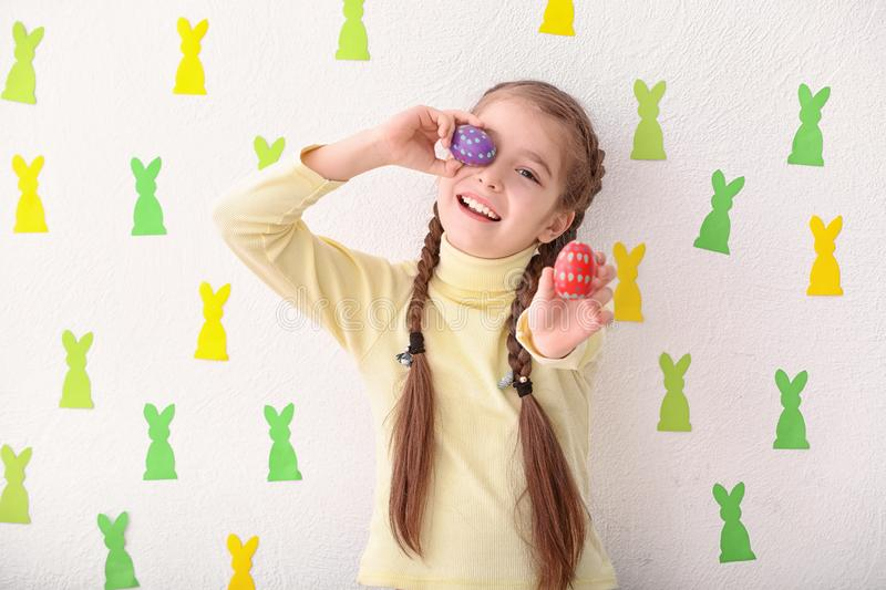 Cute little girl holding Easter eggs near white wall decorated with paper bunnies stock photo
