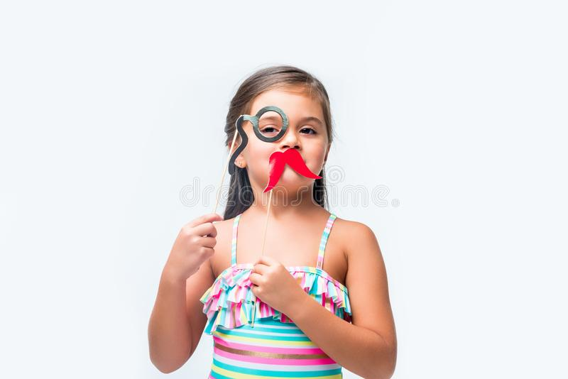 cute little girl holding false moustache and monocle on party sticks royalty free stock image