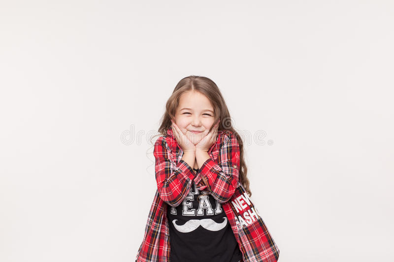 Cute little girl holding hands on her chin and smiling stock images