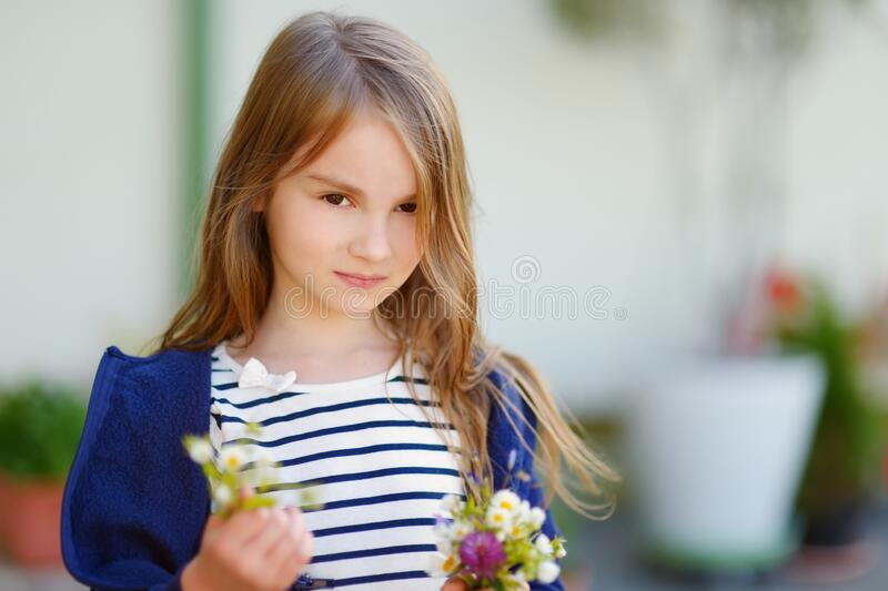Cute little girl holding small flowers bouquet on sunny summer day. Child and flowers, summer, nature and fun royalty free stock photo