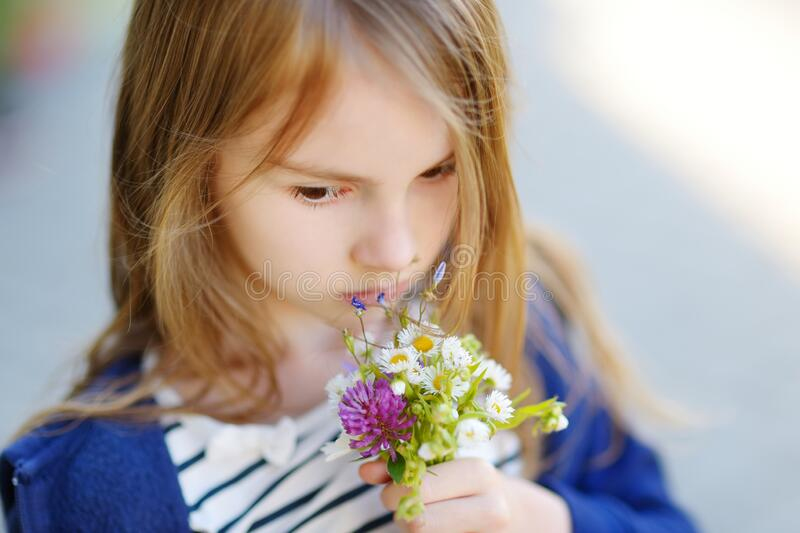 Cute little girl holding small flowers bouquet on sunny summer day. Child and flowers, summer, nature and fun stock image