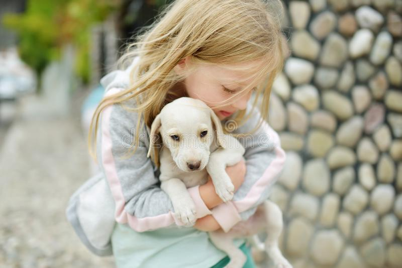 Cute little girl holding small white puppy outdoors. Kid playing with baby dog on summer day stock photos
