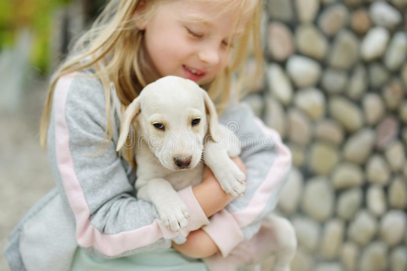 Cute little girl holding small white puppy outdoors. Kid playing with baby dog on summer day. Domestic animals and pets for children royalty free stock photos