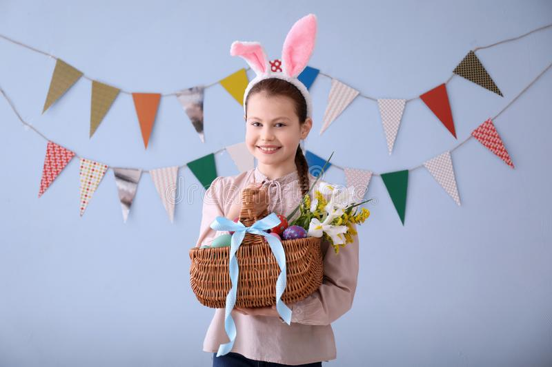 Cute little girl holding wicker basket full of Easter eggs near wall decorated with party pennants stock photo