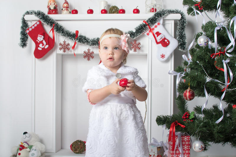 Cute little girl holds a red apple near New Year Christmas tr royalty free stock image
