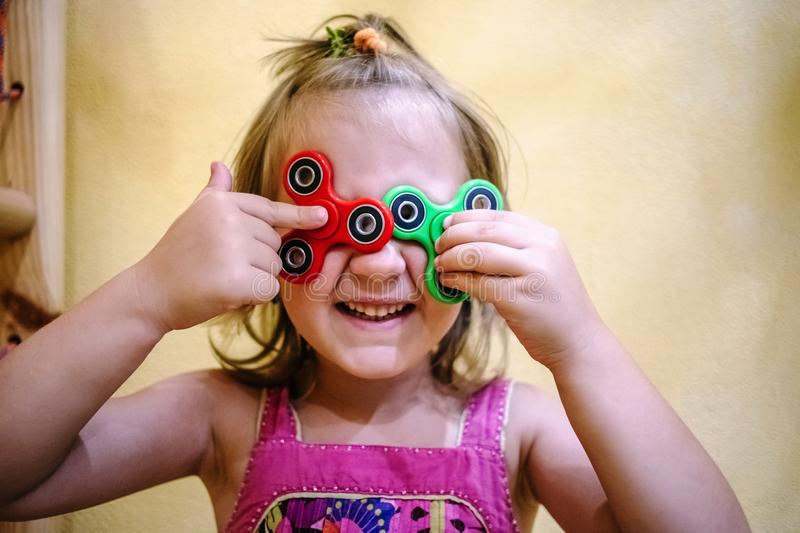 Little girl holds two fidget spinners on her face. Cute little girl holds two fidget spinners on her face royalty free stock photography
