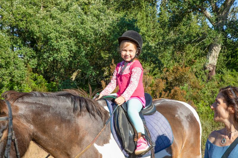 Cute little girl on a horse looking smiling next to her mother royalty free stock images