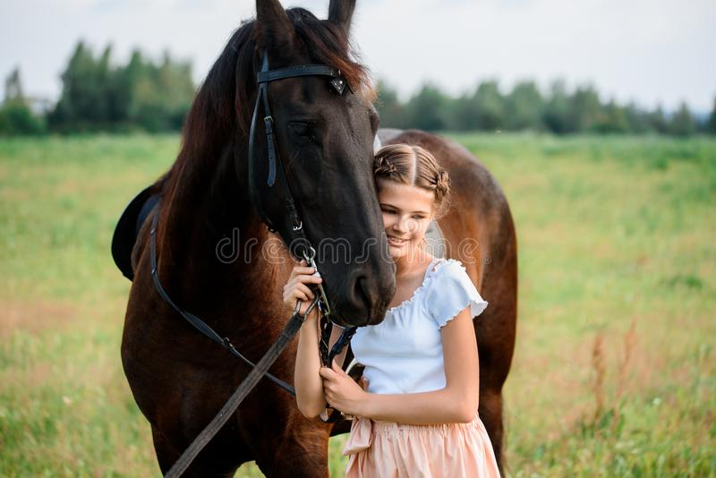Cute little girl on a horse in a summer field dress. sunny day.  stock photo