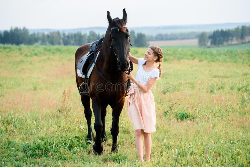 Cute little girl on a horse in a summer field dress. sunny day royalty free stock images