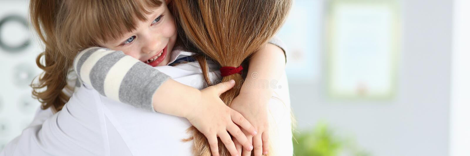Cute little girl hugging female doctor in her office royalty free stock photos