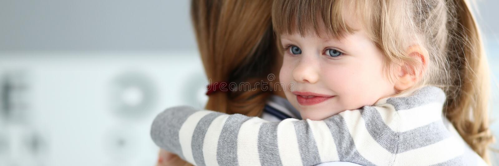 Cute little girl hugging female doctor in her office stock images