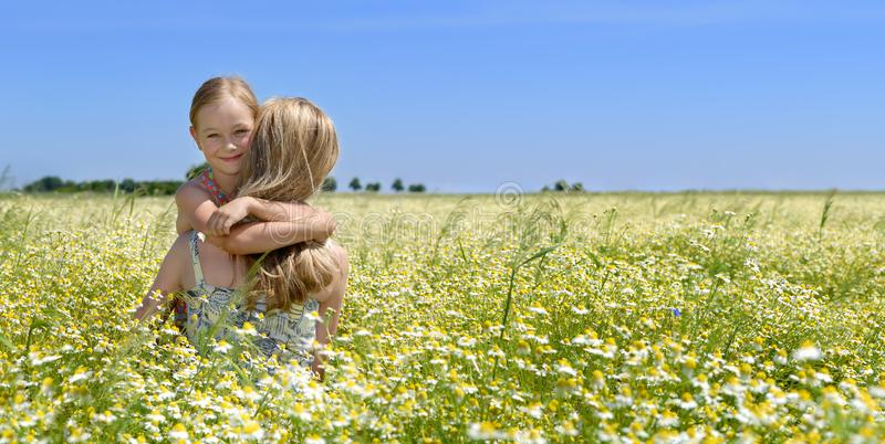 Cute little girl hugging her mom on the flowery meadow royalty free stock photography
