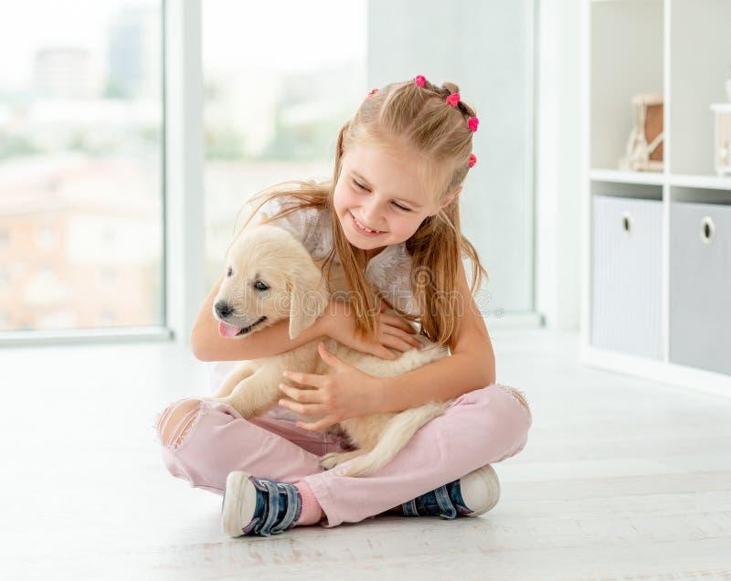 Little girl hugging retriever puppy. Cute little girl hugging retriver puppy at home royalty free stock image